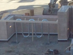 Adjacent to the new sidewalk is an enclosure for a bike rack.